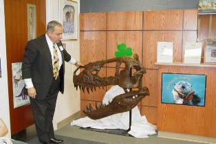 Larry James presents an elementary school with a replica of a dinosaur head. Click to enlarge