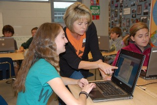Seventh grade social studies teacher Michelle Satterfield assists a student with researching an American History topic.  Click to enlarge