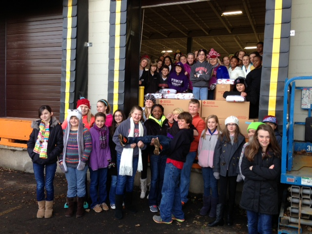 group of Greenville Middle students standing at the back of a semi truck loaded with supplies