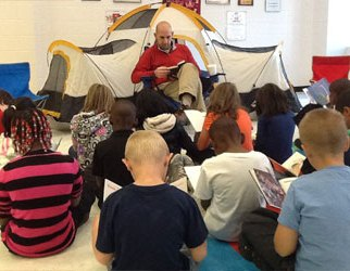 "Using the theme, ""Camping Out with a Good Book,"" Mr. Miller is reading in the school lobby with students."