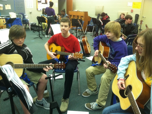 group of 3 male and 1 female students playing guitars