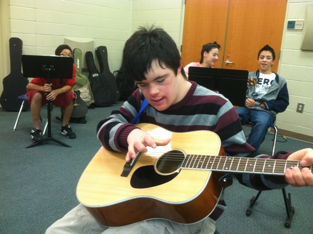 male student playing guitar