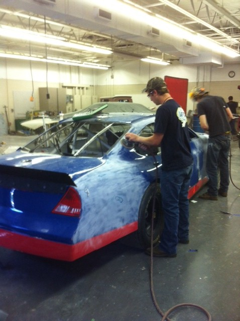Enoree auto collision repair students sanding down the race car.3
