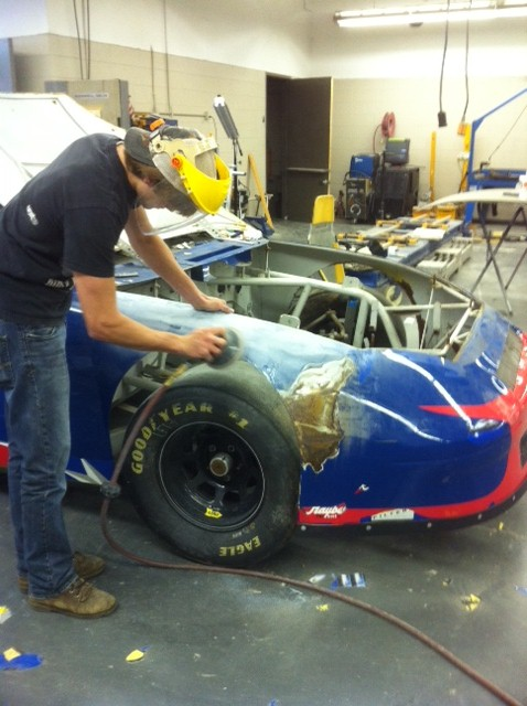 Enoree auto collision repair students sanding down the race car.2