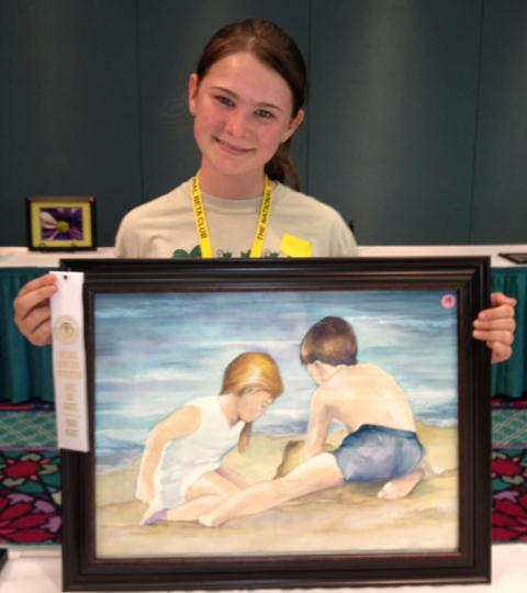 female student posing with her drawing