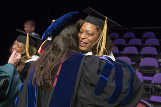 Lillian Brock Flemming Honored at Furman University Convocation hugging another graduate