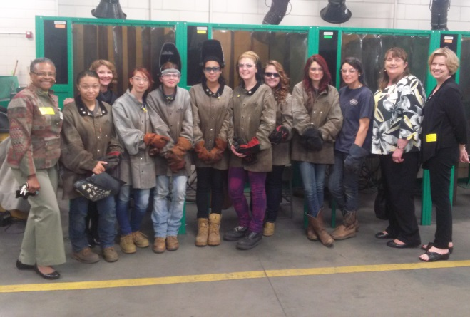 School Board members Glenda Morrison-Fair, Joy Grayson, Debi Bush, and Danna Rohleder pose for a picture with female students in the J. Harley Bonds welding program.