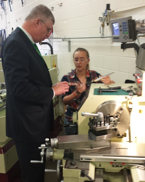 Superintendent Burke Royster observes a student's work on a machining lathe at J. Harley Bonds Career Center.