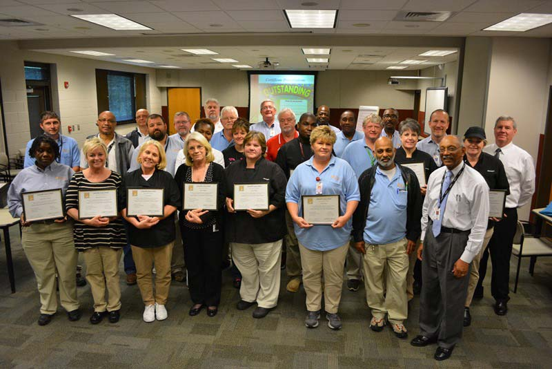 large group of operations managers and supervisors holding plaques #2