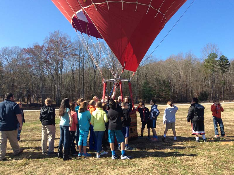 students gather around hot air balloon