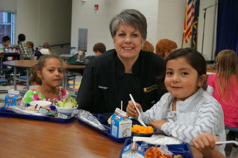 Paris Elementary Cafeteria Manager Jacque Holliday with two female students