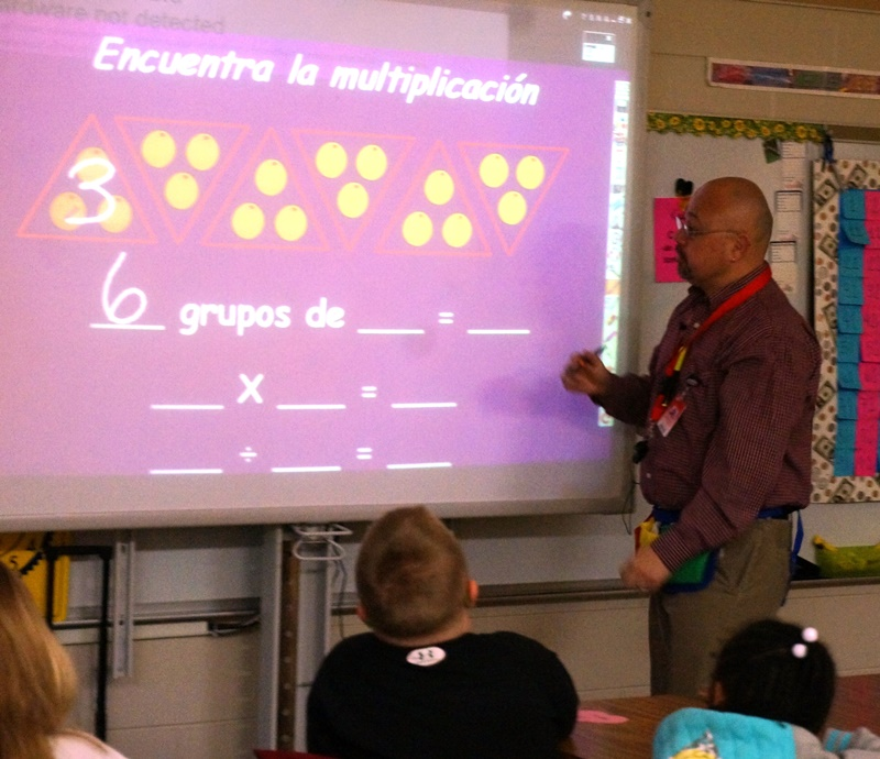 Elementary male teacher using smartboard to teach lesson