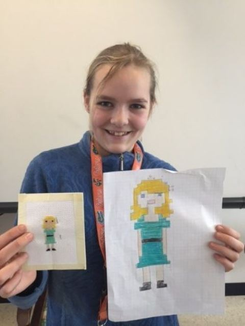 female student with two cross stitch examples