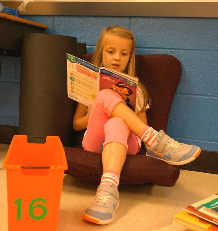 Elementary student sitting, reading a book