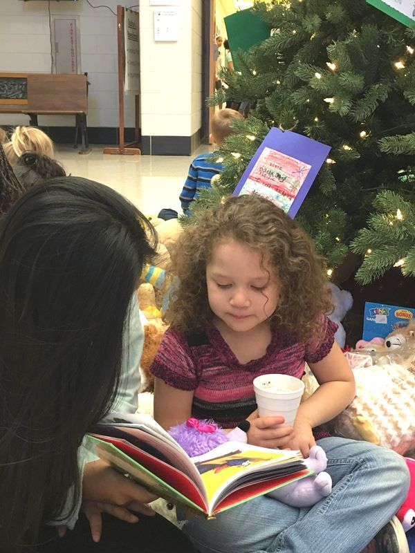 Female Sevier Middle student reading with female Paris Elementary student