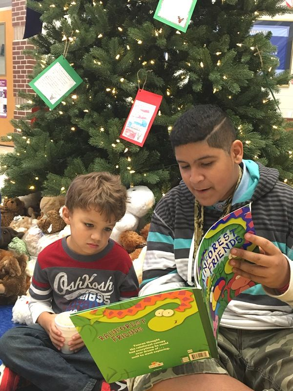 Male Sevier Middle student reading with male Paris Elementary student