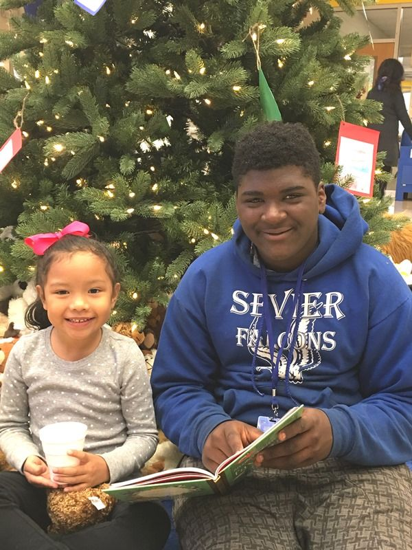 Male Sevier Middle student reading with female Paris Elementary student 2