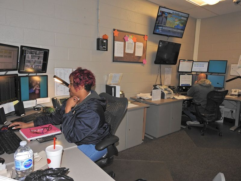Female employee sitting at security monitors