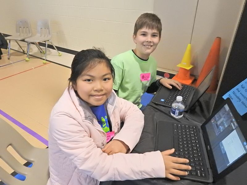 girl and boy student sitting in front of a laptop computer