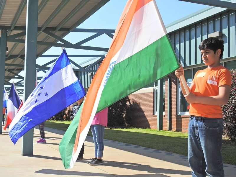 Students holding country flags in the parade of nations