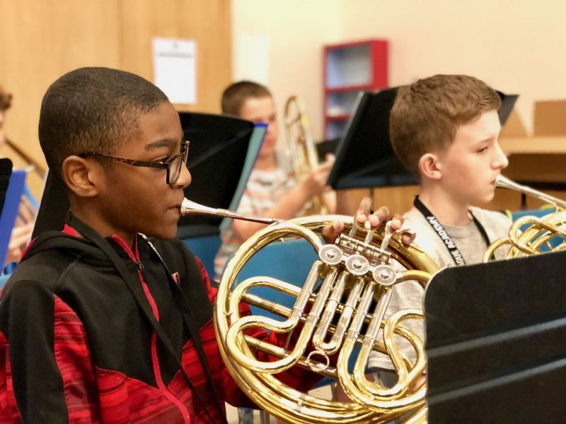 two male students playing horns
