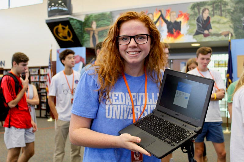 Girl holding a laptop computer at the college fair