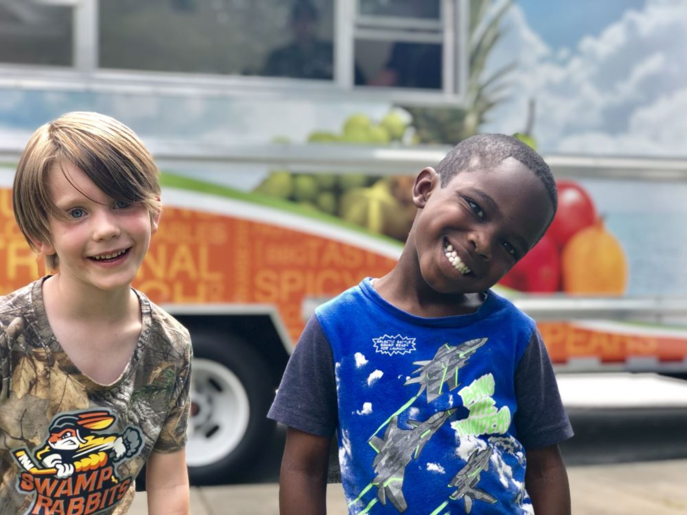 2 smiling student in front of food truck