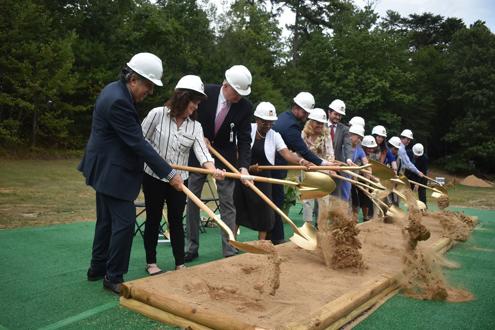 Group of people with shovels and hard hats breaking ground