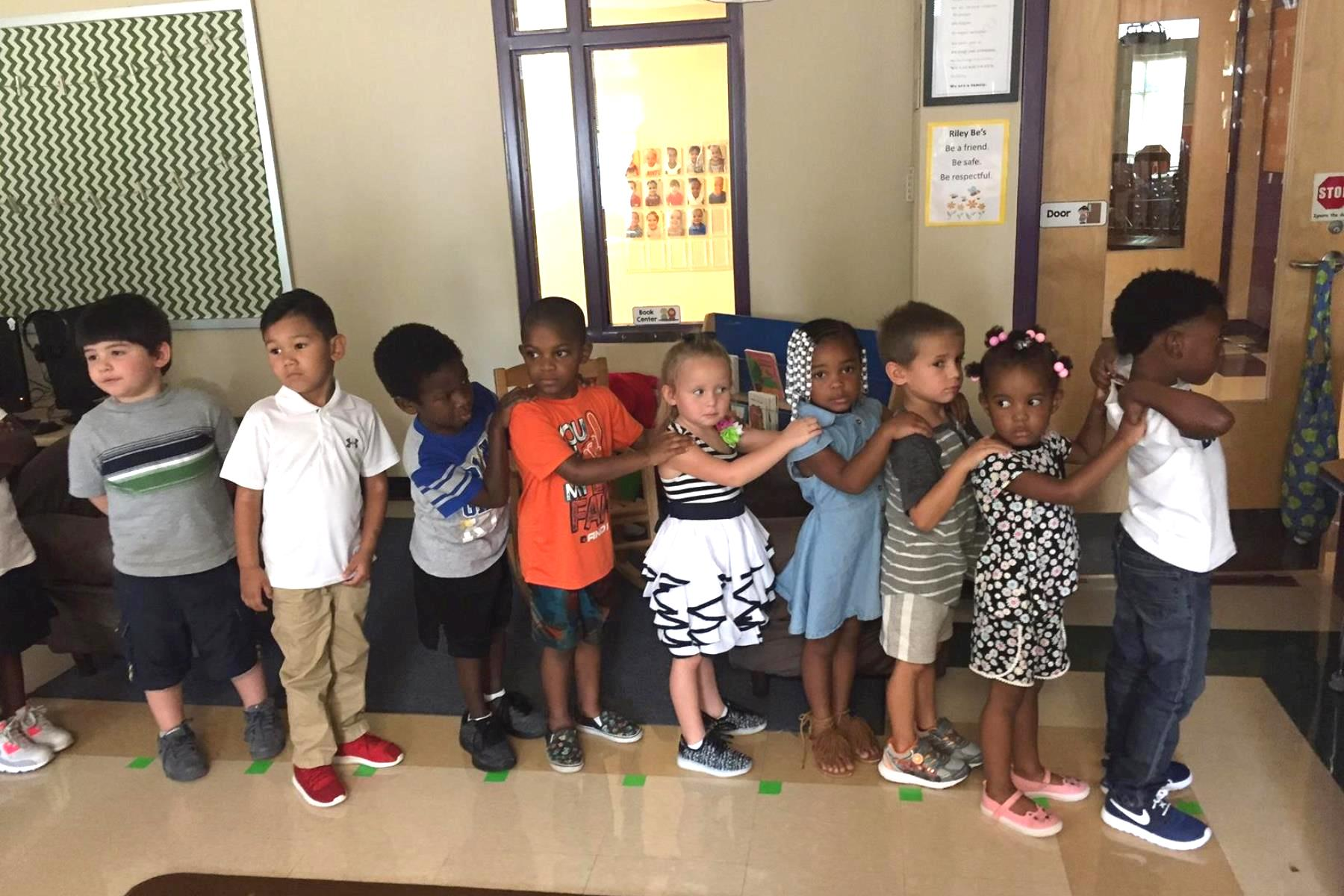 A group of pre-school children standing in a line