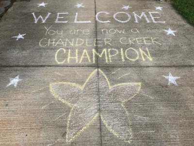 Chalk drawing on the sidewalk that says welcome to chandler creek