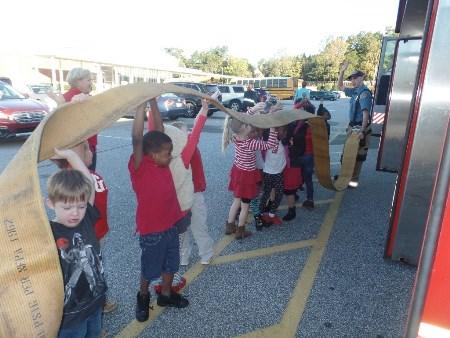 kindergarten students hold a firehose