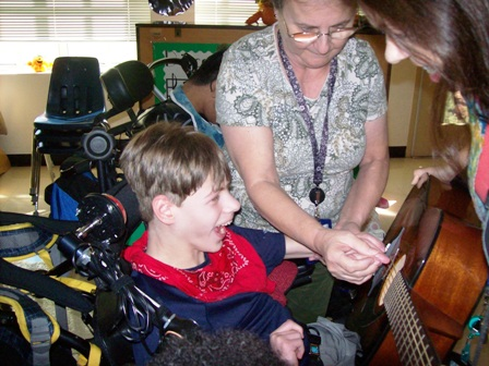 Washington Center student Noah Cronic enjoys the sounds of a guitar with Para-Educator Sandy McDowell thanks to a Donor's Choose grant to Music Teacher Julie Dail.
