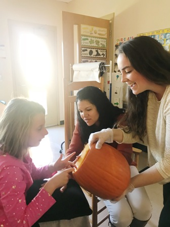 With the assistance of teachers Linda Kemp and Ryana Smith-Wilson, Washington Center student Laci Robison explores the inside of a pumpkin to find seeds during the class Fall Fest celebration.