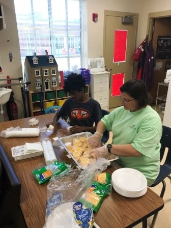 Washington Center student Vijay Rangwalla helps measure cheese into serving cups with the assistance of Daily Living Teacher Sarah Ashworth.  Mrs. Nardia Lloyd's class serves meals for the staff through the school's Seagull Grill meal preparation instructional program.