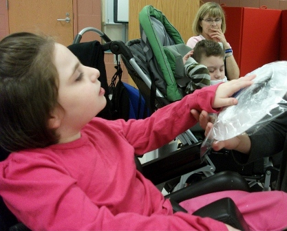 Washington Center student Kayla Radi reaches high to mix the colors for her moon during Adaptive Art class.